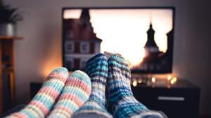 Fotografía de una pantalla de dos personas viendo la televisión