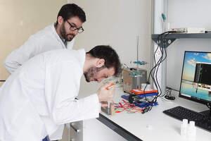 Dos investigadors duen a terme anàlisis en un laboratori, amb un ordinador sobre la taula