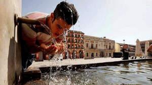 Un hombre veviendo agua en plena ola de calor en España