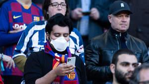 Un aficionado del Barça con una mascarilla para prevenir el coronavirus