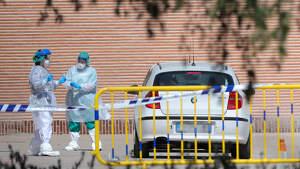 Imagen de dos profesionales de la salud conversando al lado de un coche con los trajes de protección