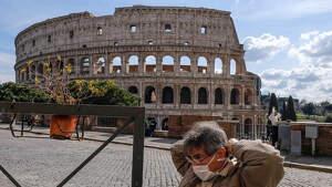 Un hombre se pasea con mascarilla delante del Coliseo en Roma