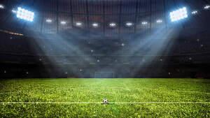 Imagen de un campo de fútbol con la pelota en el centro del campo