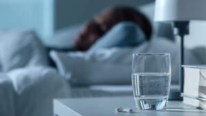 Imagen de un vaso y unas pastillas y una persona durmiendo de fondo