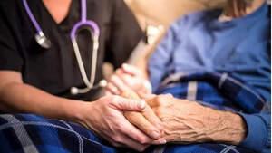 Enfermera de ciudados paliativos con una señora mayor