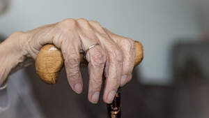 Mano de una anciana apoyada en un bastón