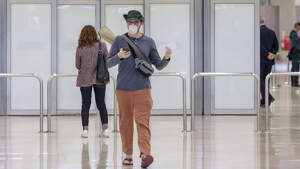Una persona con mascarilla y guantes en un aeropuerto.