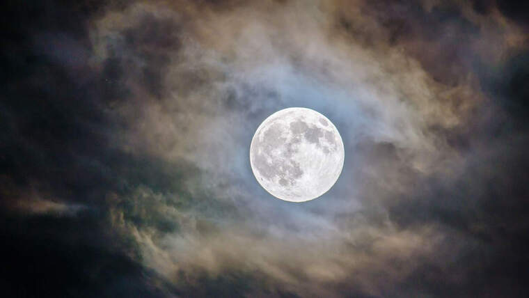Picture of a full moon in a dark sky surrounded by clouds