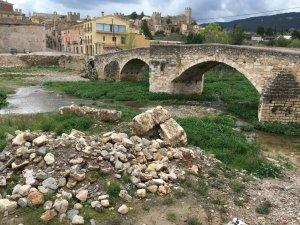 Vista del Pont Vell amb alguns fragments del mur medieval descobert fa uns mesos en primer terme.