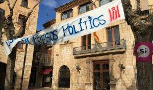 La pancarta que estava al balcó de l'Ajuntament de Montblanc s'ha reubicat entre els arbres de la plaça.