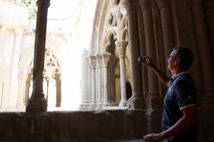 Un turista fotografiant el claustre del monestir de Poblet.
