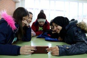 Pla mig d'un grup d'alumnes mirant un mòbil a l'institut de Valls, durant la nevada.
