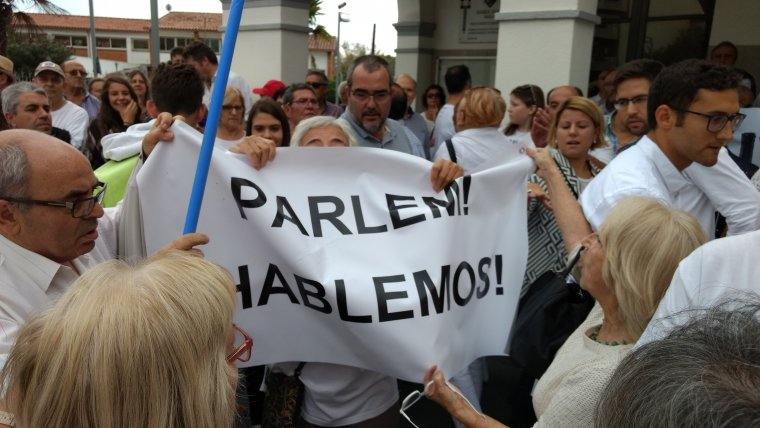 Dos dels manifestants intenten callar amb una pancarta a favor del diàleg una altra veïna.