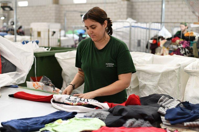 Persona treballant a la planta on es classifica la roba