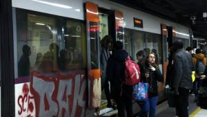 Un tren de Rodalies a l'estació de Sants amb viatgers pujant i baixant del comboi