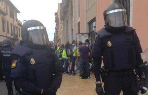 La policia espanyola entrant a l'edifici per una porta lateral als Serveis Territorials d'Urbanisme de Tarragona després d'haver trencat el vidre.