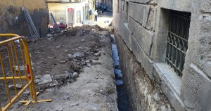 Sota la rasa lateral del carrer es pot veure la roca llisa del circ romà.