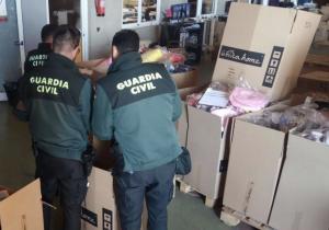 Tres agents de l'Institut Armat inspeccionant el material decomissat.