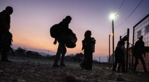 Un grupo de refugiados cruza un recinto vallado.
