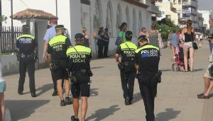 Agents de la policia i els Mossos, vigilant els manters a Coma-ruga.