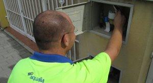 Un operari d'Aqualia revisant un comptador d'aigua.