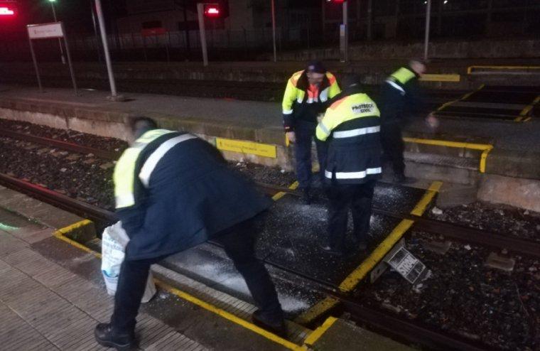 Membres de Protecció Civil i policia local de l'Arboç tirant sal a la via del tren.