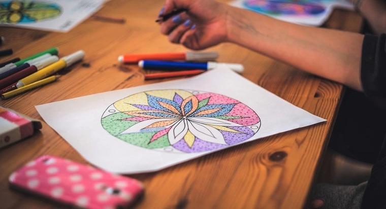 Chica coloreando una mandala en una mesa de madera