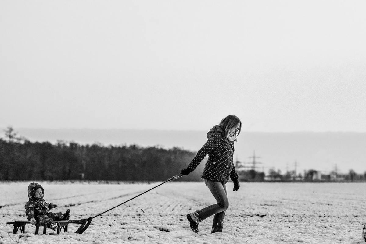 Madre jugando con su hijo en la nieve