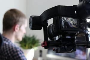 Periodista grabando con la cámara una entrevista