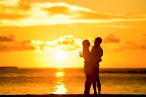 Pareja en la playa con la puesta de sol