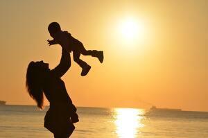 Mujer levantando a su hijo frente al mar y la puesta de sol