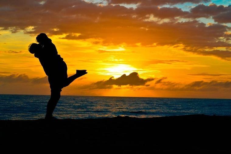 Pareja besándose con una puesta de sol al fondo