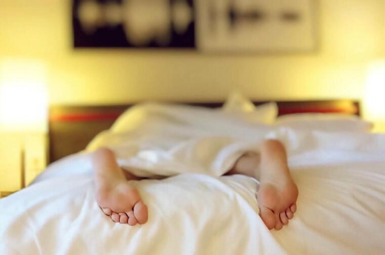 Una persona estirada en la cama con los pies desnudos