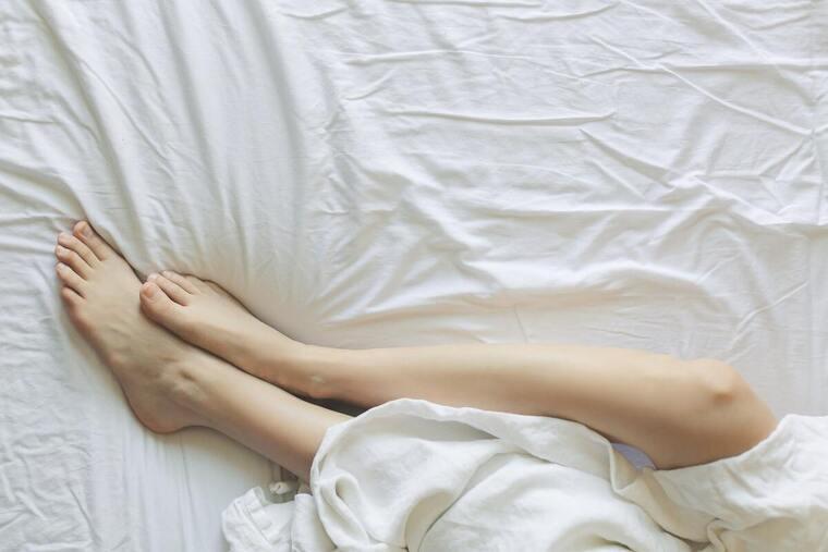 Chica con las piernas desnudas encima de una cama
