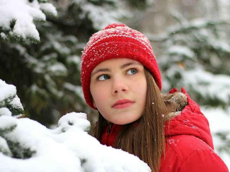 Chica con un gorro rojo en la nieve