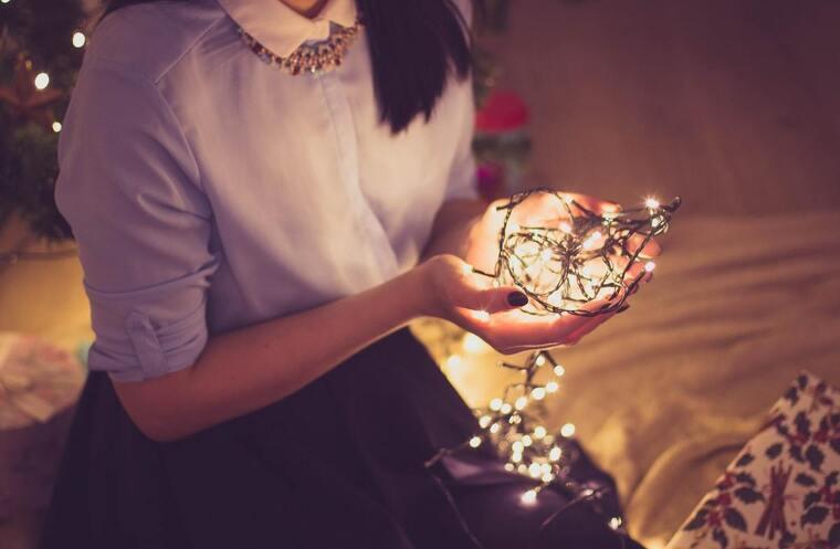 Chica sentada en la cama cogiendo luces de Navidad