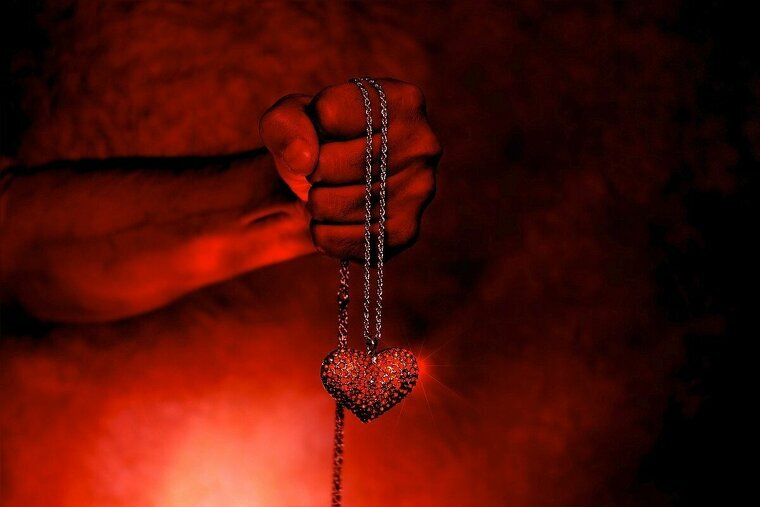 Una mano sujeta una forma de corazón en humo rojo
