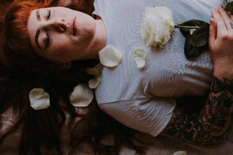 Chica con tatuajes durmiendo con flores