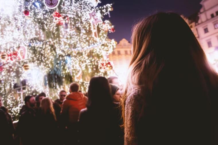 Chica frente al árbol de Navidad en la calle