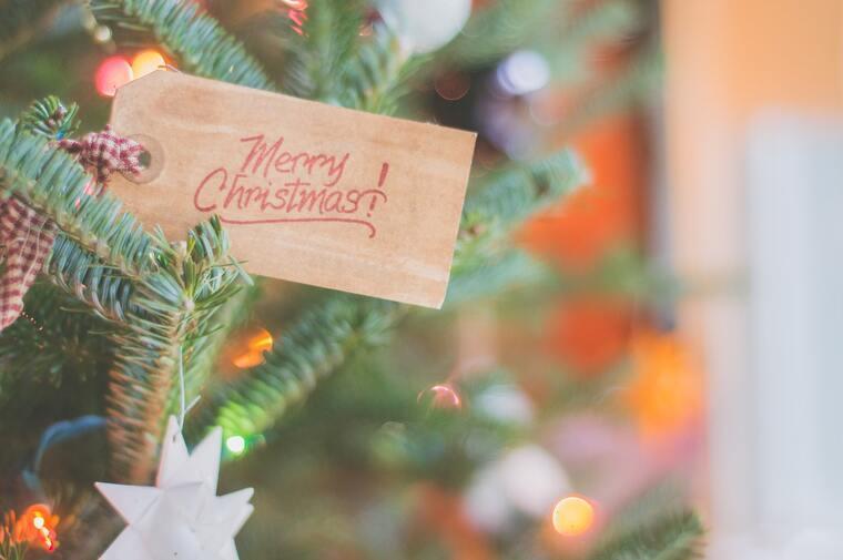Cartel de Feliz Navidad en inglés en el árbol