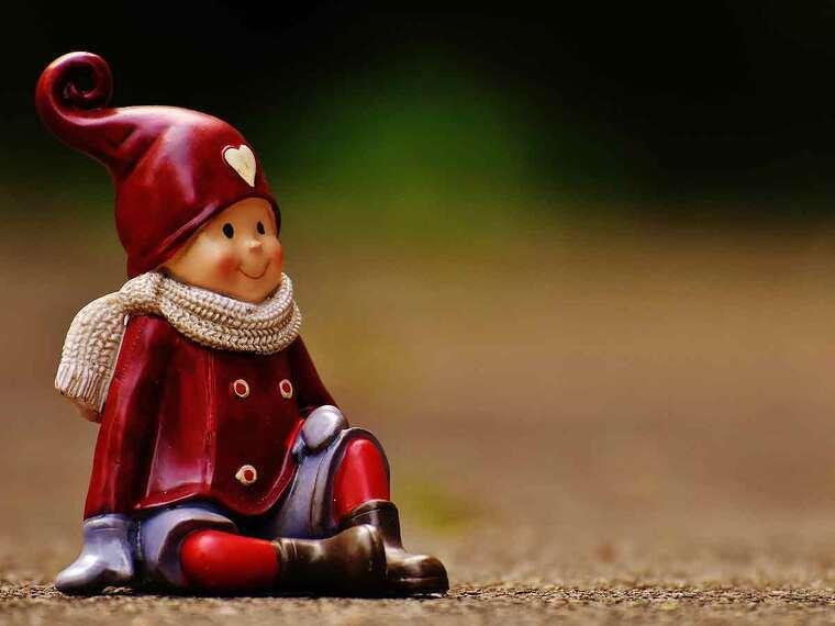 Un muñeco de porcelana sentado en la tierra