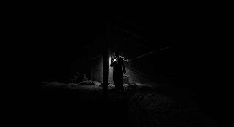 Hombre en la oscuridad con una linterna