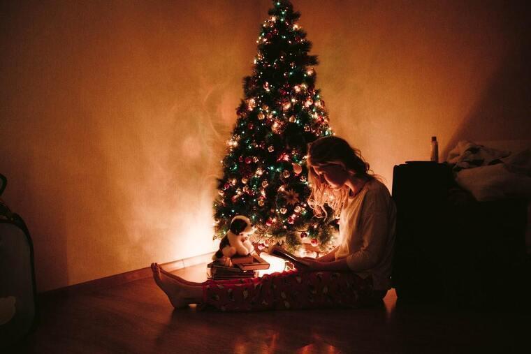 Chica leyendo al lado del árbol de Navidad