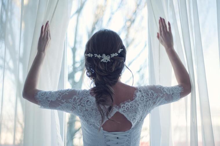 Mujer vestida de novia mirando por la ventana