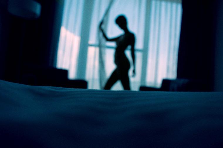 Chica posando entre la ventana y la cama