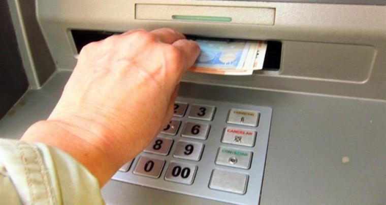 Imatge d'arxiu d'una persona traient diners d'un caixer