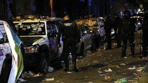 Els agents observen els cotxes malmesos davant la seu d'Economia.