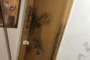 La porta del pis on van trobar mort Carles Malet, amb les marques de la Unitat Científica dels Mossos.