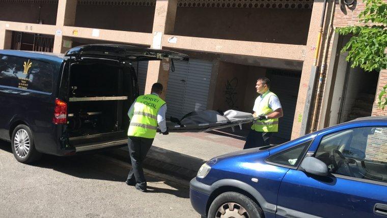 Imatge d'operaris retirant el cos de la dona del carrer de Solsona, a Badalona.