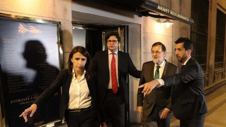 Rajoy, abandonant el restaurant amb el seu seguici